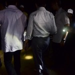Party workers light the way for Anwar as he walks up to the ceramah spot.